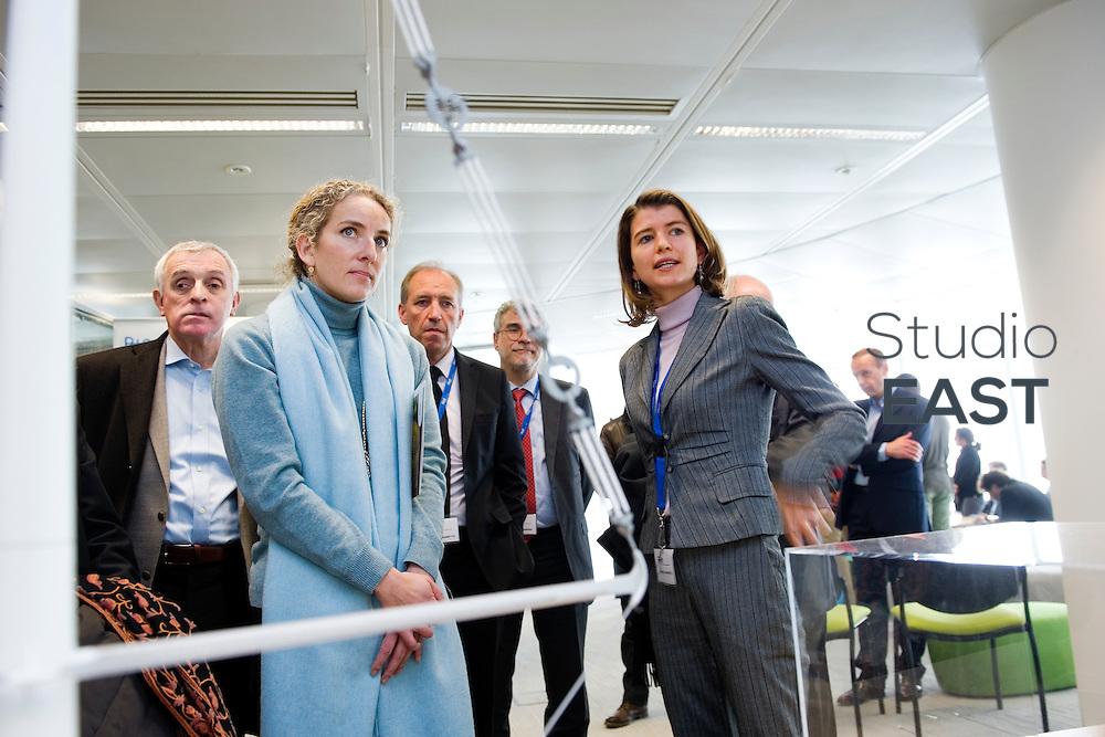 Mme Delphine Batho (centre, écharpe bleue), ministre de l'environnement et de l'énergie, regarde des modèles prototypes de pylônes électriques dans le showroom Recherche et développement de RTE, à Puteaux, près de Paris, France, le 30 mars 2013. Photo : Lucas Schifres
