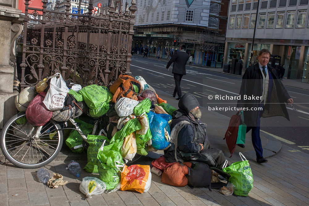 As passers-by walk by, a homeless man sits with all his worldly possessions on Piccadilly in central London.