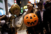 A young woamn dressed in a costume carries a jack o latern bag to collect candy as she celebrate Halloween in Shibuya, Tokyo, Japan. Thursday, October 31st 2013