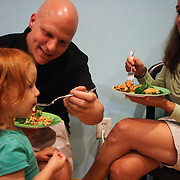Curt Altarac, left, feeds his daughter Nina Altarac, 2, as her mother Jennifer Hildreth looks on during the Wilmington Vegan Dining Guide Release Celebration Sunday August 3, 2014. The event featured vegan doses by local restaurants and businesses and a silent auction. (Jason A. Frizzelle)