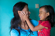 Jula Eha  at home with one of her daughters.<br /> <br /> Jula runs a small shop from the front of her house in a quiet residential area near the town of Bogor, Indonesia.<br /> <br /> Her shop had mixed success at first and she used to become demotivated, but after subscribing to Usaha Wanita she regained her motivation and started to think of more creative ways to make her business a success. <br /> <br /> As a result her profits have increased and she is now saving money in an education fund for her children. <br /> <br /> She has also been able to follow Usaha Wanita's advice on savings and investments and she has joined a savings scheme and purchases new fridges and display cabinets for her store.