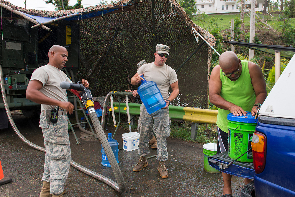 Comerio, PR, November 11, 2017--Luis Duran Vega collects 50 gallons of water from a water purification station set up near Comerio, PR by the National Guard.  Duran makes the 20 minute drive every other day for water for his family of five every two days. The National Guard division 139 BSB is from South Dakota and have been in Puerto Rico since October 8th. This station distributes 40,000 - 60,000 gallons a day in Comerio. Photo by Lori Waselchuk/BRAF