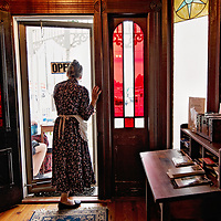 Docent Barbara Connolly peers out the front door of the John Blue House in Laurinburg, N.C., Saturday, October 7, 2017. The doors throughout the home display decorative stained glass and the color is only visible from the inside.