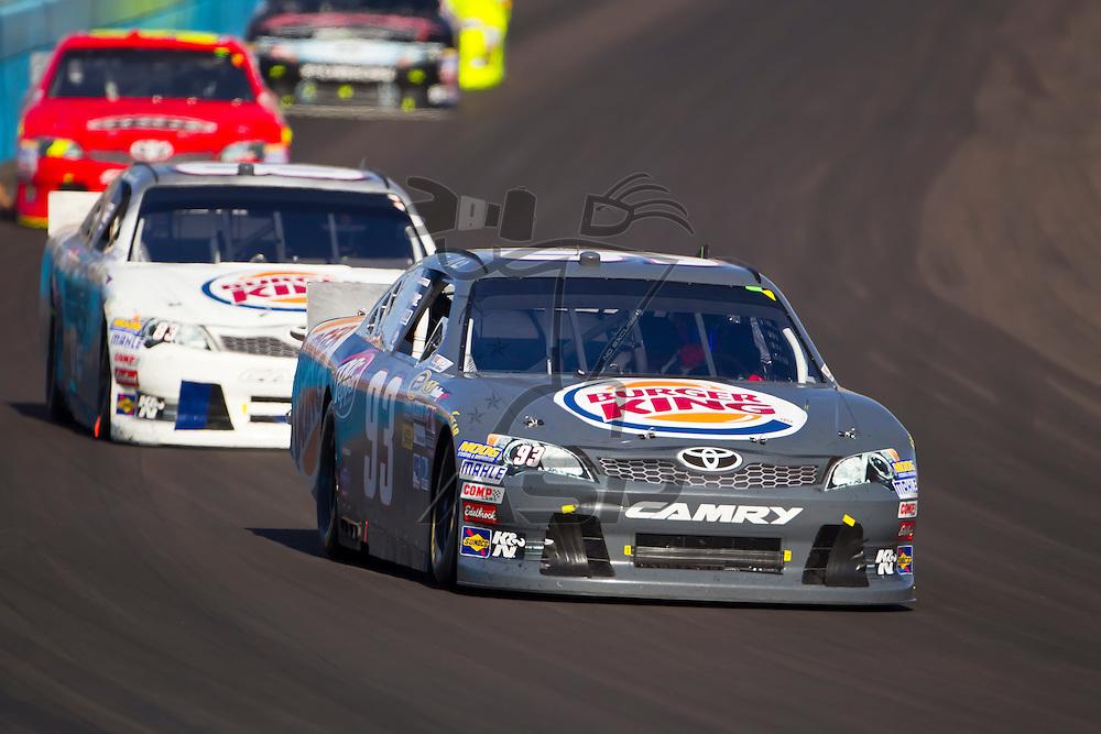 AVONDALE, AZ - MAR 04, 2012:  Travis Kavapil (93) and Landon Cassill (83) bring their cars through turn 1 during the Subway Fresh Fit 500 race at the Phoenix International Raceway in Avondale, AZ.