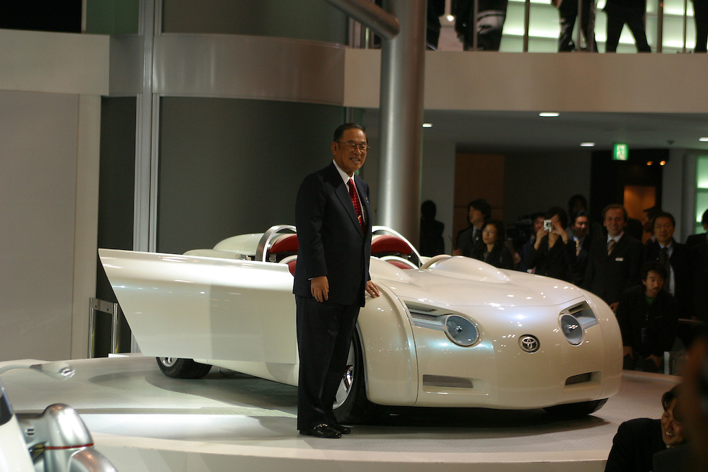 Toyota President Fujio Cho stands infront of a  concept car at the  2003 Tokyo Motor Show.©peterblakely 2004  all rights reserved.