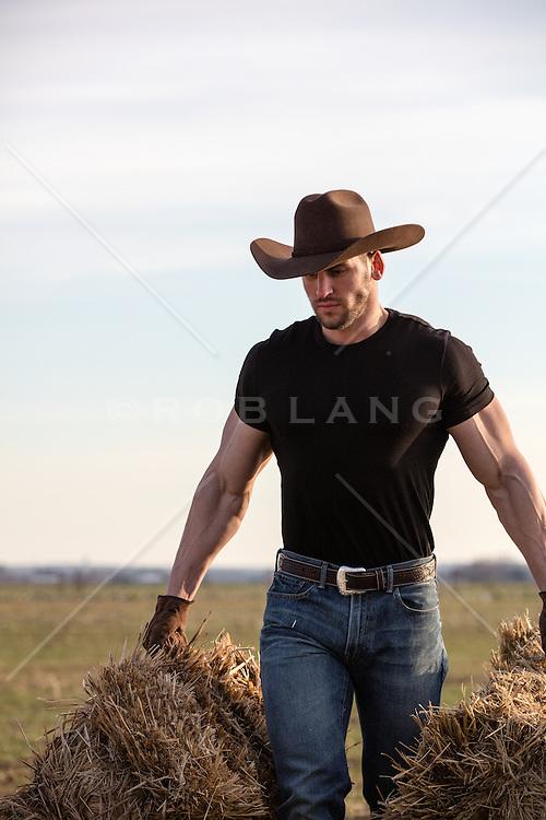 muscular cowboy lifting bales of hay on a ranch