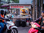 24 MARCH 2017 - BANGKOK, THAILAND: Motorcycle taxis pass a soup vendor's cart on Sukhumvit Soi 69 (Phra Khanong). The soup vendor is facing probable eviction. Food cart vendors along Sukhumvit Road between Sois 55 (Thong Lo) and 69 (Phra Khanong) in Bangkok have been told by city officials that they have to leave the area by 17 April. It's a part of an effort by Bangkok city government, supported by the ruling junta, to take back the city's sidewalks. The evictions in the area are the latest in mass evictions of Bangkok street food vendors after similar actions elsewhere on Sukhumvit, in the Ari area, in Silom/Patpong and Ratchaprasong neighborhoods. The vendors in Thong Lo/Phra Khanong are popular with local office workers because most of the formal restaurants in the area serve foreign tourists and upper class Thais and are very expensive. The street food carts serve meals starting at about 35Baht ($1US). The city has not announced if they will provide alternative locations for the carts.     PHOTO BY JACK KURTZ
