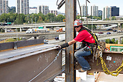 Journeyman ironworker Bree Smith works steadies a beam as the other end is secured while erecting the steel structure of the Knight Cancer Research Building in southwest Portland.