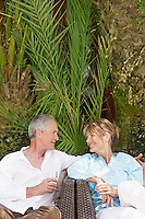 Middle-aged couple sitting outdoors on chairs talking