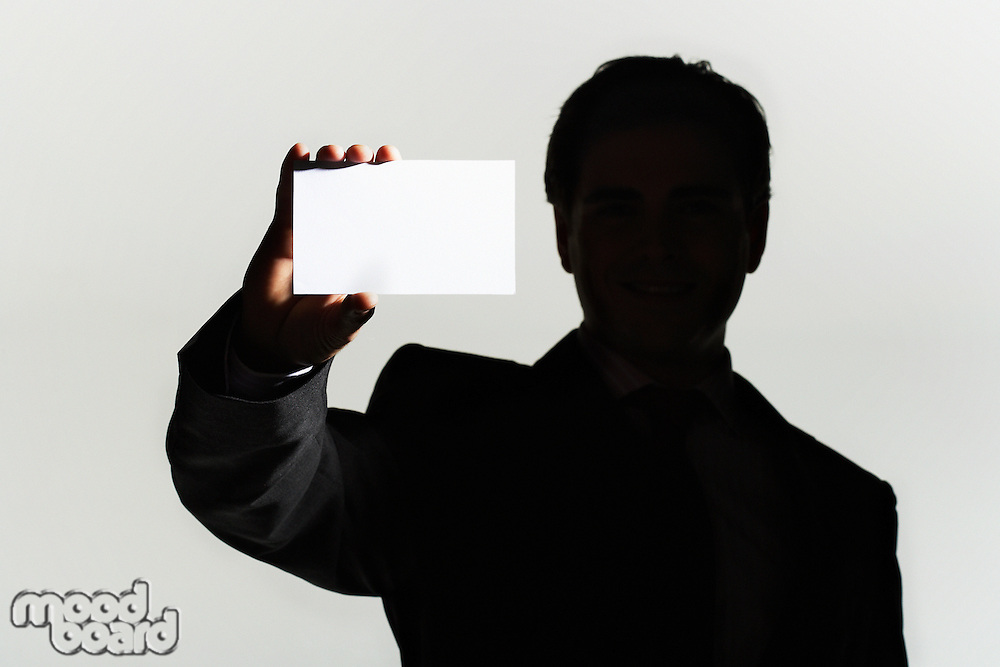Silhouetted man standing holding large blank card