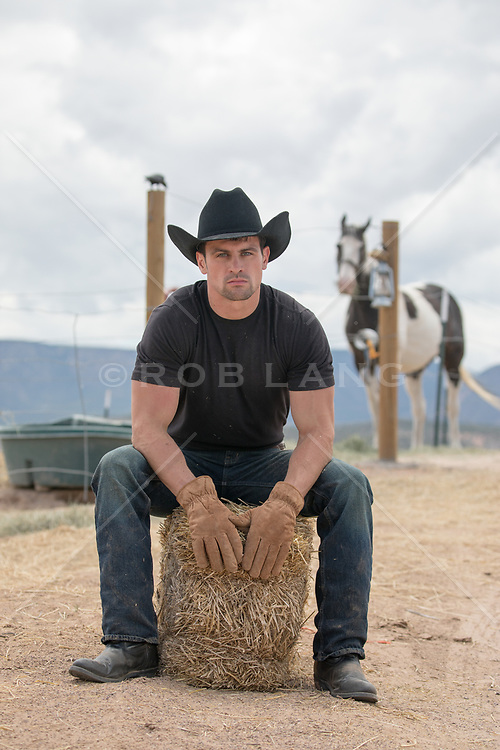hot man with green eyes and black hair in an open tuxedo shirt and tie hot cowboy on a ranch sitting on a hay bale