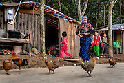 A woman walks past her home in Manhenuan village, Xishuangbanna, China.  With the financial success of the nearby Dai minority cultural village at Olive Dam, residents of Manhenuan are trying to open their village up to tourism as well.