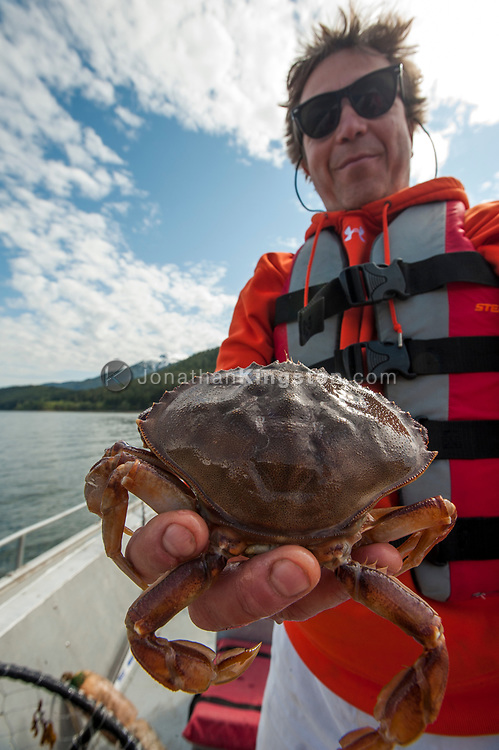 Close-up of a man holding a crab on a boat near Juneau, Alaska.