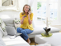 Woman holding credit card using phone in living room elevated view