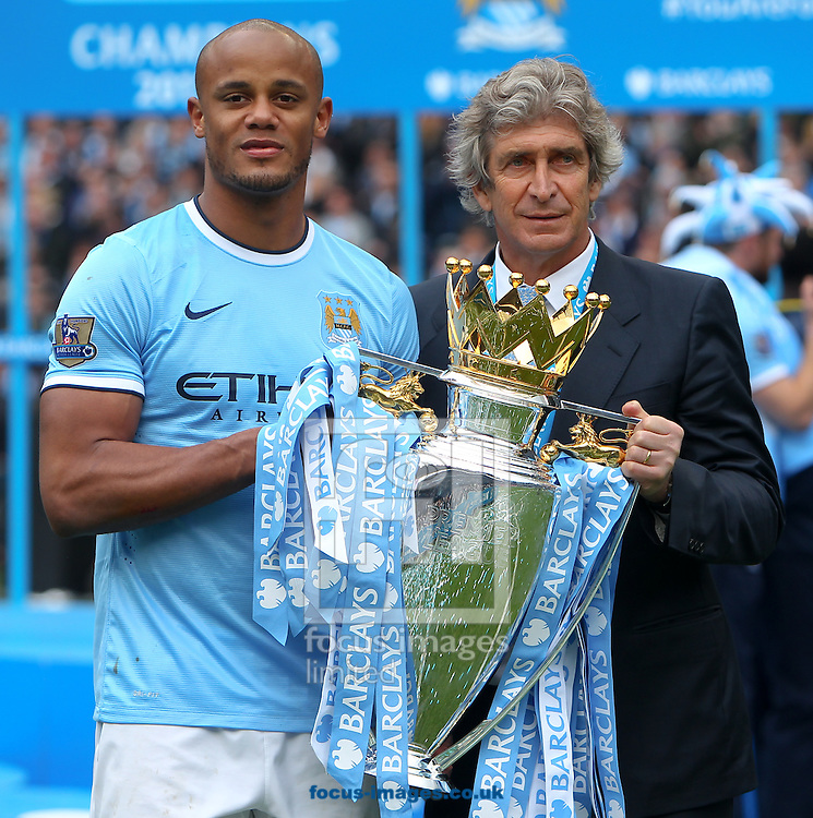Vincent Kompany and manager Manuel Pellegrini of Manchester City acelebrate with the Barclays Premier League trophy at the Etihad Stadium, Manchester<br /> Picture by John Rainford/Focus Images Ltd +44 7506 538356<br /> 11/05/2014