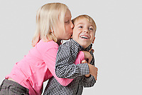 Young girl kissing and embracing brother over white background