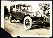 man sitting in the car on a dirt road USA 1924