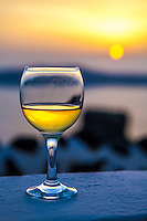 A glass of white wine at sunset, Imerovigli, Santorini, Greece