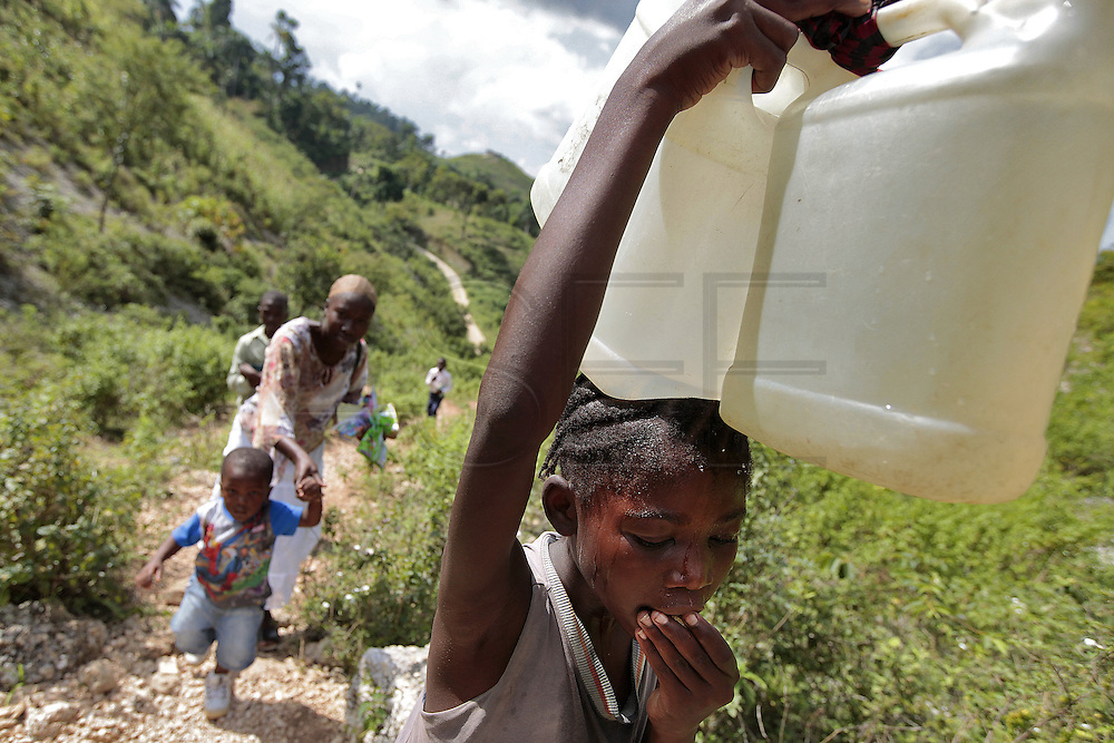 A young girl makes her way back home with two containers filled with water after collecting it at the natural spring atop the mountain above Carrefour, Haiti.  Behind her a family makes their way back up the mountain after attending church service.