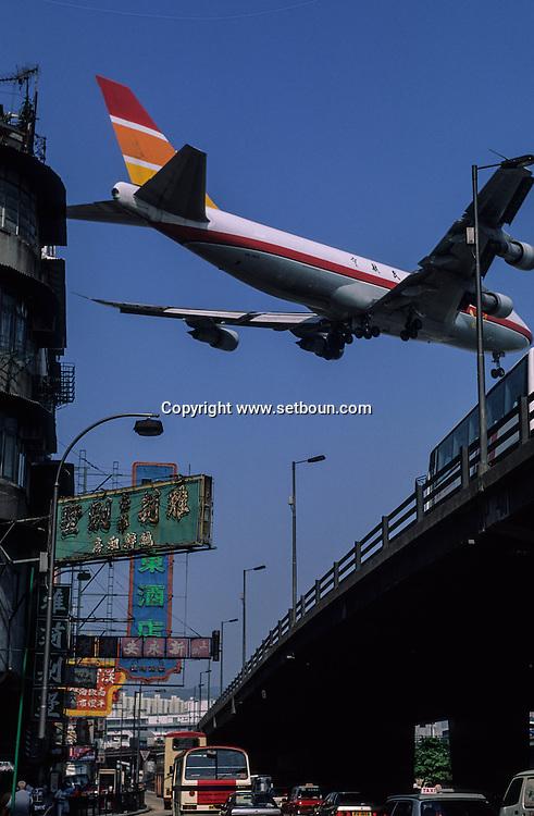 Hong Kong. Plane Flying Over Buildings A plane flies low over the Ma Tau Wai area of Kowloon, ., planes landing on Kai tak airport in the city CENTER over the buildings .      / Des avions au ras des buildings. Avion atterrissant en plein milieu de la ville sur L'ANCIEN aéroport  DE Kai Tak (QUARTIER MONGKOK) / Dans la ville de Hong-Kong surpeuplée, l'avion est le principal moyen d'accès à la ville. La seule piste d'atterrissage est en pleine ville       / R82/25    L1074  /  R00082  /  p0006066