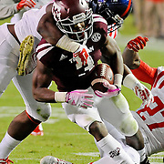 Mississippi defensive end Channing Ward (11) tackles Texas A&M running back Trey Williams (3) during the second half of an NCAA college football game in College Station, Texas, Saturday, Oct. 11, 2014. No. 3 Mississippi won 35-20. (Photo/Thomas Graning)