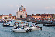 "Every year during Redentore Festival weekend, Venice builds a temporary pontoon bridge for pedestrians to walk 330 meters across Giudecca Canal from the Zattere to Redentore basilica on Giudecca Island, Italy. Venice built ""Il Redentore"" (Church of the Most Holy Redeemer, or Chiesa del Santissimo Redentore) from 1577-1592 on Giudecca Island in Venice Lagoon, in thanksgiving for the end of a 1576 wave of plague. Redentore Festival (Redentore Festa, photo July 16, 2011) began as a feast of thanksgiving for the end of the terrible plague of 1576 which killed more than a quarter of Venice, some 46,000 in the city and 94,000 in the lagoons. (A worse round of Black Death swept Venice in 1629-30, after which Venice built the Salute, the last of its ""Plague churches."") The religious celebration and popular feast of Redentore is held in Venice every the third Saturday and Sunday in July, with fireworks on Saturday night. Venice (Venezia), the ""city of canals,"" is the capital of Italy's Veneto region, named for the ancient Veneti people from the 10th century BC. Venice and the Venetian Lagoons are on the prestigious UNESCO World Heritage List."