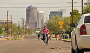 South Tucson resident Alba Davis cycles to work on a Sunday morning through the southside community, Tucson, Arizona, USA.