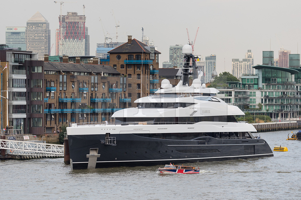 © Licensed to London News Pictures. 04/07/2018. London, UK.  A small union jack covered boat passes the new 243 feet long superyacht, Elandess, which arrives in London for the first time ever on the River Thames and moors at HMS President, the Royal Navy Reserve Unit next to St Katharine Docks and Tower Bridge this evening. Elandess was built at the Abeking and Rasmussen shipyard in Germany, launched in May 2018 and has just completed sea trials ahead of its London visit. Elandess has an axe-bow, dark hull and low-slung superstructure. There are a variety of entertaining communal spaces, from the 8 x 2.5-metre superyacht swimming poollocated on the massive sun deckto the Nemo Loungewith portholesbelow the waterline and an observation lounge on the upper deck. Guest accommodation includes six staterooms, including the master suitewhich is placed forward on the main deck with an observation lounge directly above on the upper deck.  Photo credit: Vickie Flores/LNP