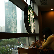 Shanghai, China: Modern Chinese relaxing at a Starbucks in a shopping centerat the tip of Lujiazui in the Pudong district on the shores of Huangpu River. Jose More Photography
