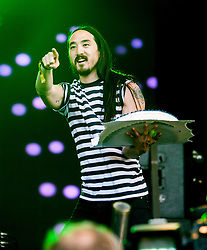 """Steve Aoki with his cake, playing the main stage, Saturday at Rockness 2013, the annual music festival which took place in Scotland at Clune Farm, Dores, on the banks of Loch Ness, near Inverness in the Scottish Highlands. The festival is known as """"the most beautiful festival in the world"""" ."""