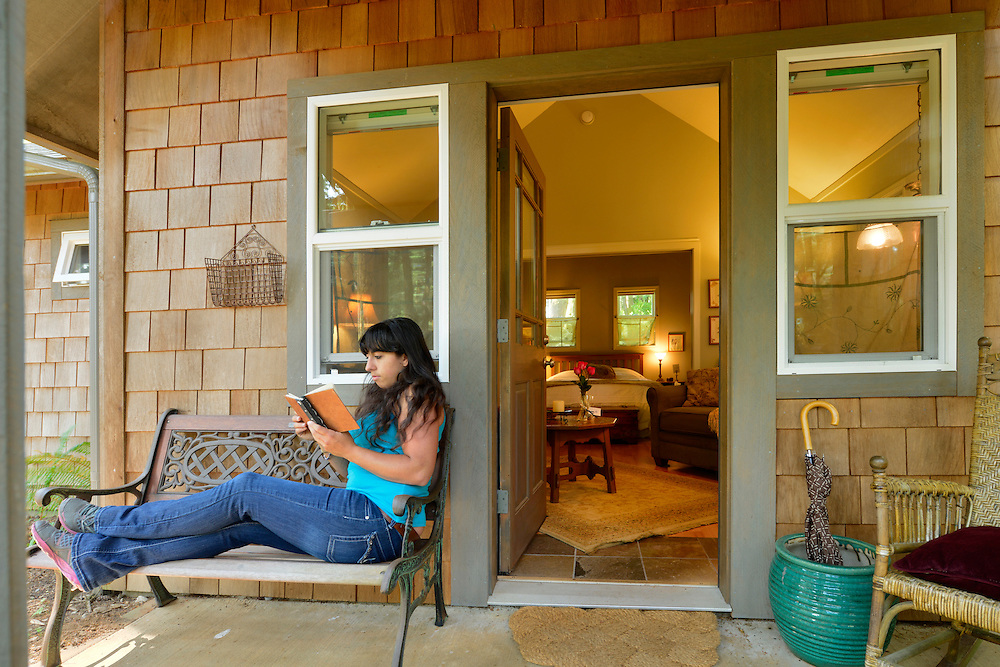 Woman reading in front,Guest Cabin, Wildspring Guest Habitat, Port Orford, Oregon, USA<br /> Model release 0247