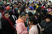 A large group of Hmong people is gathered in front of the Xiang Khoang (Xieng Khouang) post office awaiting remittance from relatives who reside in the United States of America (USA). The Hmongs living in the United States today came from Laos, a small landlocked country in mainland Southeast Asia. Each month thousands of Hmong-Americans send money to the relatives they left behind after the Second Indochina War.  This ethnic group originated from the Chinese provinces of Yunnan, Guizhou, Sichuan, & Hunan. .