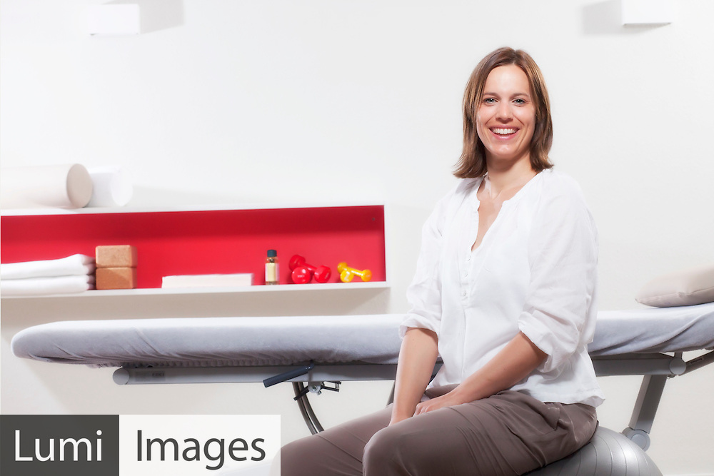 Female osteopath sitting in Physiotherapy Practice, Munich, Bavaria, Germany