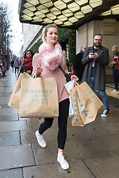 © Licensed to London News Pictures. 22/12/2017. London, UK. A woman with several shopping bags walks along Oxford Street in London on the last Friday before Christmas. Photo credit: Vickie Flores/LNP