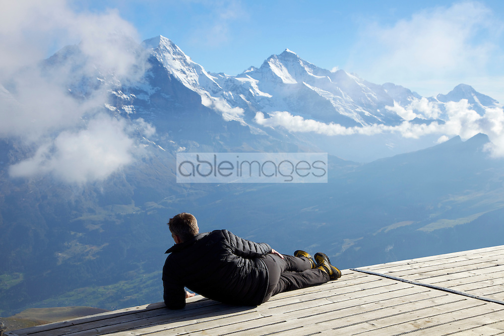 Back View of Man Lying on Viewing Platform Looking at Alpine Landscape