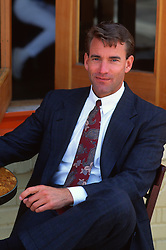 Man wearing a suit, shirt and tie, seated with his legs crossed at an outdoor table