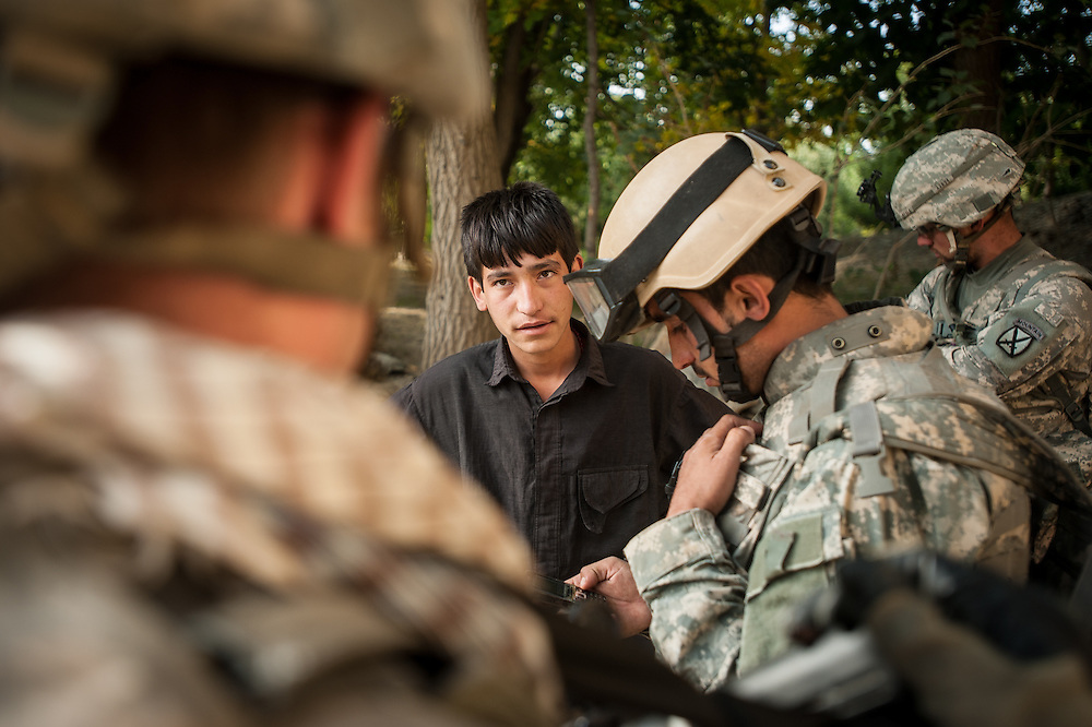 An Afghan interpreter and American soldiers interrogate an Afghan boy in the Jalrez Valley of Wardak Province.