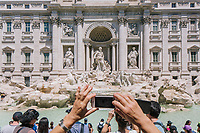 """ROME, ITALY - 20 JUNE 2017: A tourists photographs the Trevi fountain with her smartphone in Rome, Italy, on June 20th 2017.<br /> <br /> The warm weather has brought a menacing whiff of tourists behaving badly in Rome. On April 12, a man went skinny-dipping in the Trevi fountain resulting in a viral web video and a 500 euro fine.<br /> <br /> Virginia Raggi, the mayor of Rome and a national figurehead of the anti-establishment Five Star Movement,  issued an ordinance involving harsher fines for eating, drinking or sitting on the fountains, for washing animals or clothes in the fountain water or for throwing anything other than coins into the water of the Trevi Fountain, Bernini's Four Fountains and 35 other city fountains of artistic or historic significance around the city.  """"It is unacceptable that someone use them to go swimming or clean themselves, it's an historic patrimony that we must safeguard,"""" Ms. Raggi said."""