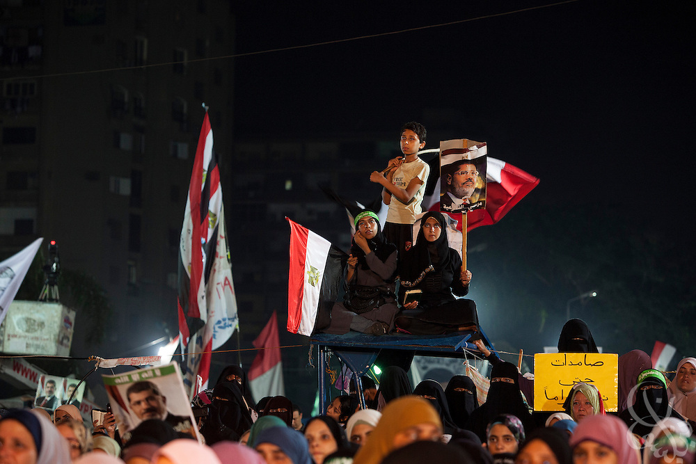 Supporters of deposed Egyptian president Mohamed Morsi cheer as they listen to various speakers on a stage inside the large sit-in around the Rabaah al-Adawia mosque and square in the Nasr City district of Cairo Friday July 28, 2013.  They remain defiant in spite of nearby clashes earlier in the day that killed at least 65 pro-Morsi demonstrators and wounded thousands.
