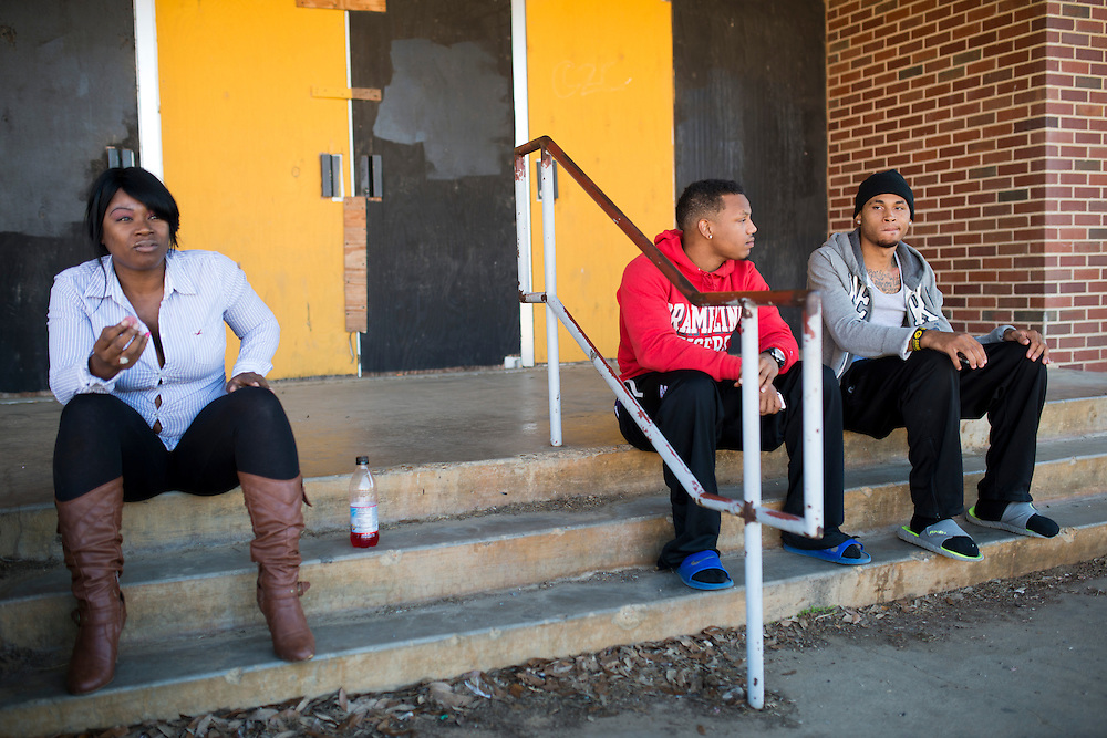 """(L to R) Kasey Brown, Kyle Simon and Jessie Cole hang out on the steps of the Grambling State University Natatorium in Grambling, Louisiana on October 23, 2013. The natatorium is boarded up with most windows broken out but plans to renovate the building into a new Health and Wellness Center are """"coming soon.""""   (Cooper Neill for The New York Times)"""