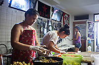 "ROME, ITALY - 3 JULY 2016: (L-R) Gipsy Queens members Darmaz Florentina (33), Maria Miglescu (20) and Aninfa Hokic (31) prepare typical Roma dishes for their food stand at the iFest, an alternative music festival, here in the Astra 19 social center in Rome, Italy, on July 3rd 2016.<br /> <br /> The Gipsy Queens are a travelling catering business founded by Roma women in Rome.<br /> <br /> In 2015 Arci Solidarietà, an independent association for the promotion of social development, launched the ""Tavolo delle donne rom"" (Round table of Roma women) to both incentivise the process of integration of Roma in the city of Rome and to strengthen the Roma women's self-esteem in the context of a culture tied to patriarchal models. The ""Gipsy Queens"" project was founded by ten Roma women in July 2015 after an event organised together with Arci Solidarietà in the Candoni Roma camp in the Magliana, a neighbourhood in the South-West periphery of Rome, during which people were invited to dance and eat Roma cuisine. The goal of the Gipsy Queen travelling catering business is to support equal opportunities and female entrepreneurship among Roma women, who are often relegated to the roles of wives and mothers."