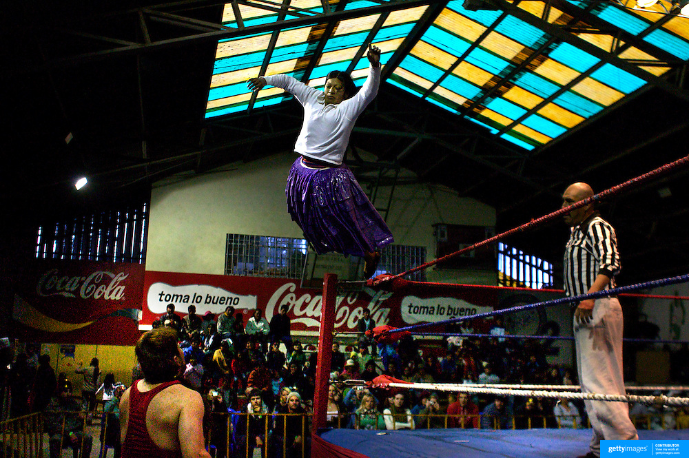 Yolanda la Amorosa dives onto her maler counterpart during the 'Titans of the Ring' wrestling group's Sunday performance at El Alto's Multifunctional Centre. Bolivia. The wrestling group includes the fighting Cholitas, a group of Indigenous Female Lucha Libra wrestlers who fight the men as well as each other for just a few dollars appearance money. El Alto, Bolivia, 24th January 2010. Photo Tim Clayton