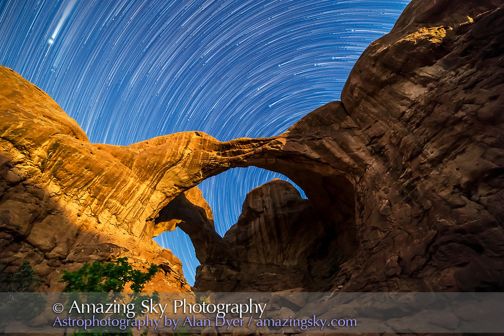 Circumpolar star trails spinning behind Double Arch at Arches National Park, Utah, as the waning gibbous Moon lights the arches toward the end of the sequence. The Big Dipper is streakng into frame at top right from behind the butte at right, while Jupiter is the bright object at top left streaking down into the scene. <br /> <br /> During the shoot, other photographers were lighting the Arches but this did not affect my shoot, as my foreground came from near the end of the shoot after they had all left and I had natural illumination to light the Arches.<br /> <br /> This is a stack of 160 frames taken over 2.5 hours from 9:30 to midnight, starting in moonless darkness, then brightening as the Moon rose in the last hour of the shooting, lighting the sky and arches. The nearest arch casts its shadow onto the distant arch, with its shadow shape matching the other arch.<br /> <br /> The frames were stacked with Star Circle Academy&rsquo;s &ldquo;Advanced Stacker Actions&rdquo; for Photoshop using the Long Streaks effect. The foreground comes from a stack of 8 frames for noise reduction, taken toward the end of the shooting with the moonlight illumination. An additional frame taken a couple of minutes after the last star trail frame adds the short unstreaked stars at the head of the trails. <br /> <br /> Each exposure was 45 seconds at f/2.8 and ISO 3200 with the Canon 6D and 14mm Rokinon lens. Dark frames taken at the end of the night (8 stacked in Mean combine for a master dark) were also subtracted from each of the foreground and star trail stacks, which reduced noise speckling.