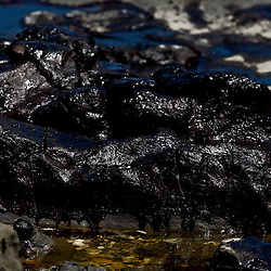A thick black oil coats parts of the beach in Port Fourchon, Louisiana, U.S., on Tuesday, May 25, 2010. The BP Plc Deepwater Horizon drilling rig that exploded and collapsed into the Gulf of Mexico continues to release thousands of barrels of oil into the gulf as cleanup and containment efforts continue all along the gulf coast from Louisiana to Florida. Natural wildlife habitats along with marine life are threatened by oil that is now reaching coastal areas throughout Louisiana. Photographer: Derick E. Hingle
