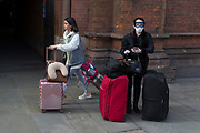 As the UK government urged that all Britons should avoid non-essential travel abroad in order to combat the Coronavirus pandemic in Britain, a female passenger wearing a face mask and ski goggles checks her phone outside St. Pancras rail station, the terminus for Eurostar services to mainland Europe, on 17th March 2020, in London, England.