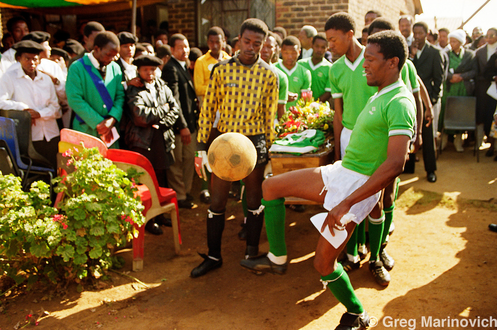 Mourners play with a football at the funeral of one of their teammates killed in political clashes. Soweto, South Africa, 1990/1.
