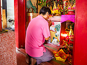 """05 SEPTEMBER 2017 - BANGKOK, THAILAND: A man prays at spirit house in Bangkok's Chinatown district on Hungry Ghost Day. The Ghost Festival is a Buddhist and Taoist holy day celebrated on the 15th day of the 7th lunar month. It is primarily celebrated in China and Chinese communities outisde China. In Thailand, it's celebrated in Thai-Chinese communities in Bangkok, Phuket and Chiang Mai.  On that day ghosts and spirits, including those of the deceased ancestors, come out from the lower realm to visit the living. Families prepare elaborate banquets for the spirits and burn """"ghost money"""" for the spirits to use in the other realm. It is a day for venerating dead relatives.      PHOTO BY JACK KURTZ"""