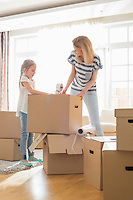 Mother and daughter packing cardboard boxes at home