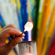 A Paiwan glass bead takes form with colorful glass rods used to make designs in the background at Dragonfly Bead Art Studio, Sandimen, Pingtung County, Taiwan