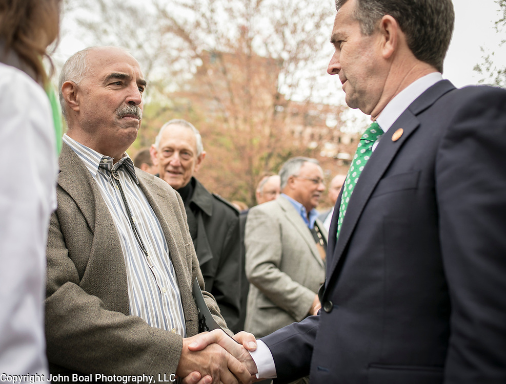 Virginia Governor Ralph Northam, right, greets Ken Branham, former Chief of Monacan Nation, during the dedication ceremony for Mantle: Virginia Indian Tribute, a monument designed on Virginia State Capitol Square, in Richmond, Virginia, on Tuesday, April 17, 2018. John Boal Photography